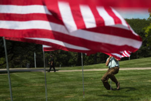 Ride captain with Patriot Guard Riders Mike Hendrick uses his bodyweight to plant a flag in the ground Wednesday, August 8, 2018, at Memorial Park in Omaha, Nebraska.