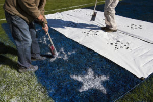 Painters (from left) Chad Hansen, owner of All About Grass, and John Puchalla paint stars on the American Flag in the north end zone Thursday, Oct. 18, 2018, at Lincoln Christian. Hansen thinks of every end zone design as a story, and with Veteran's Day coming up he seized the opportunity to honor them with an end zone design.
