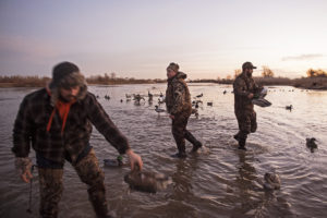 At dawn, duck hunters (from left) Pat Bendlin, Parker Ridgeway and Kyle Benesch place decoys near their hunting blind along the Platte River on Wednesday, Dec. 20, 2017, in Columbus, Neb.