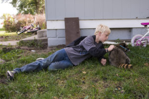 Jace Bader lays in his yard to stroke his pet raccoon Charlie on Thursday, Sept. 27, 2018, in Valparaiso prior to the arrival of Saunders County Sheriff Department and Nebraska Game and Parks. Charlie was picked up for euthanization after he bit a child. KAYLA WOLF, Journal Star