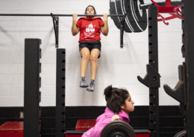 Brithany Cervantes does pull-ups in the weight room during wrestling practice Wednesday, Jan. 16, 2019, as other teammates lift at West Point-Beemer Jr.-Sr. High School.