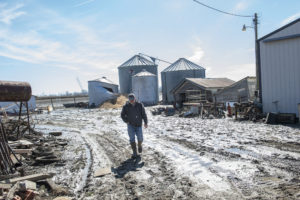 Dave Eaton walks towards the road, behind him a mess of flood-damaged grain bins, barns and machinery Friday, March 22, 2019, on his farm in the Missouri River bottomland near Union, Nebraska.