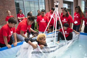 Taurus Dismuke (front left) holds on to the edge of the boat to avoid water that started to seep in once teammate Aiden Bear (right) sat in the corner of the boat Monday, June 3, 2019, during the STEM Leadership Academy at Nebraska Innovation Studio in Lincoln.
