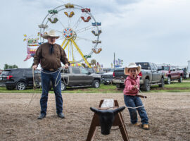 Cowboy church pastor Tim Rust teaches a young boy how to rope a steer during his sermon on Sunday, July 28, 2019, at the Hall County Fair.