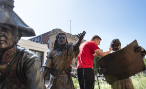 """Casey Seger a museum registrar at Great Plains Art Museum cleans and adds wax to the face of William Clark part of """"On the Trail of Discovery"""" a bronze statue by George Lundeen on Monday, July 22, 2019, on the corner of 12th and Q Streets. The statues are washed and waxed once every 6 months to a year."""