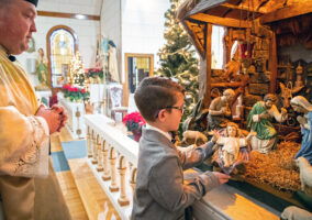 Father Benjamin Rynearson, left, watches as Justin Stava, of rural Weston, carries baby Jesus to the manger on Saturday, Dec. 24, 2019, at Saint Cyril and Methodius Catholic Church in Plasi, Nebraska.