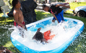 Cousins, from left, Kesaun Dupree, 6, Tyrell Sullivan, 13, and Tyvaughan Jefferson, 12, play outside Monday, July 2, 2018, at their Grandmother's house in Omaha, Nebraska.