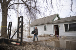 Kody Smith helps move clothes out of his flooded home Sunday, March 17, 2019, in Peru, Nebraska. The family, which is expecting a baby in a few weeks, found a home to rent in a neighboring town.