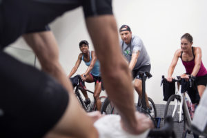 "During an early morning cycling class, instructor Gardie Jackson (foreground) barks orders at class participants (from left) Shawn Brokemond, Jason Hann and Natalie Jackson on Monday, June 4, 2018, at Five Points Fitness in Corte Madera. ""She is one of the best role models around,"" Gardie Jackson said. ""You are bound to see some magic, following her around."""