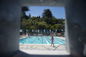 A faint reflection of Shawn Brokemond (right) glistens off of a plexiglass viewing window at the Strawberry Recreation District Pool on Sunday, June 3, 2018. Brokemond met a friend at the pool to give her some pointers to improve her swim stroke.