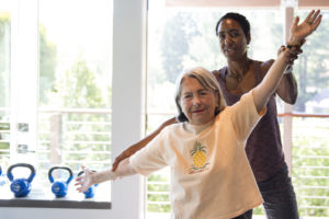 Shawn Brokemond helps her 85 year-old neighbor Ginette Davis stretch during a training session on Monday, June 4, 2018, at Brokemond's home gym in Mill Valley.
