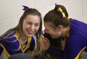 Payton Alexander tells a secret to Jerzie Menke as they hang out with a group of wrestlers and cheerleaders after a high school basketball game.