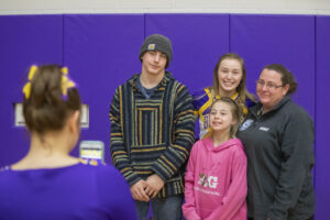 The Menke family, from left, Steven, Elizabeth, Jerzie and their mom Marsha pose for a photo after senior night following a basketball game. Jerzie's younger siblings are both wrestlers as well.