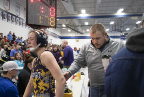 Following her loss to William Costello, Jerzie Menke leaves the mat in tears with her coach Zach Malcolm. Menke had hoped to make it to state, but after two losses her state tournament journey came to an end.