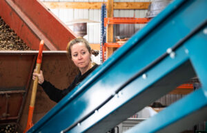 Sarah Ferdico watches as pecans make their way onto a conveyor belt to be separated from rocks and other debris before they can be cracked and sorted for packaging. Ferdico works with her dad, Charlie Willnerd, who started the pecan operation as a way to diversify his corn and soybean farm.