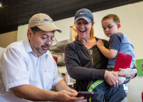 Pepe Fierro shows Sarah Ferdico, center, and Dawson Ferdico a picture of an event that Pepe's restaurant, Pepe's Bistro, held for the community following a deliver that Ferdico made on Thursday, December 6, 2019.