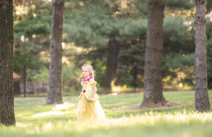 Evalee Herink walks through a grove of trees Thursday, July 11, 2019, dressed as Belle prior to the start of Beauty and the Beast at Pinewood Bowl.
