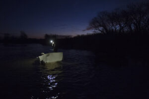 Parker Ridgeway pushes a boat of duck decoys out onto the Platte River to setup for waterfowl hunting on Wednesday, Dec. 20, 2017, in Columbus, Nebraska.