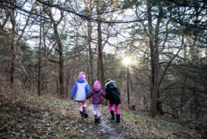 Hikers, from left, Sophie Huenink, Shelby Huenink and Olivia Clark walk through the woods with their parents, not pictured, Wednesday, Jan. 1, 2020, during the First Day Hike at Mahoney State Park.